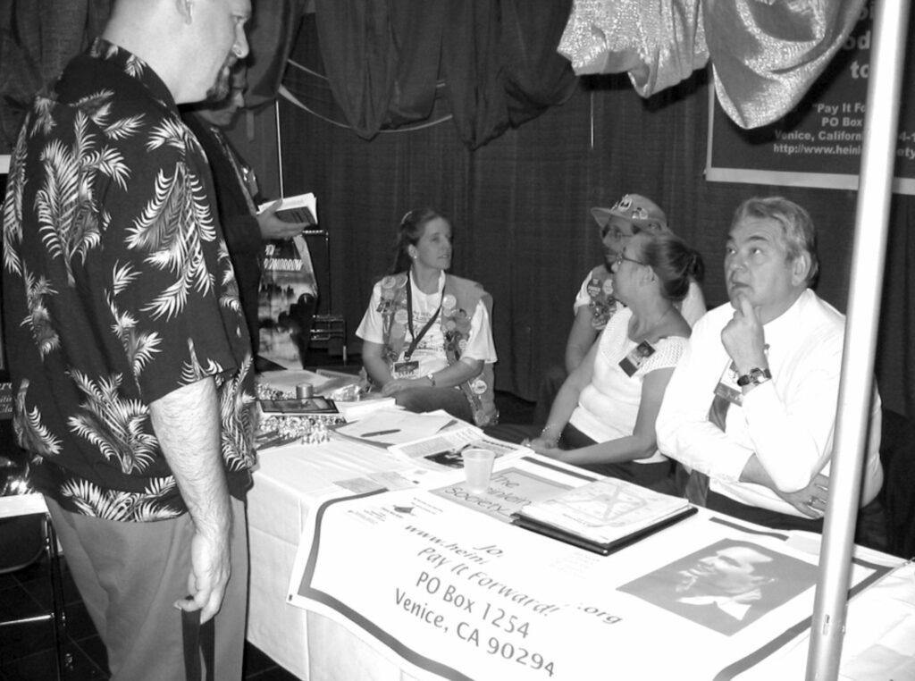 Robert James (standing) talks with Bill Patterson (seated) at the Heinlein Society table at Noreascon IV, with Alan Milner, Mike and Sharon Sheffield, Pam Somers in background.